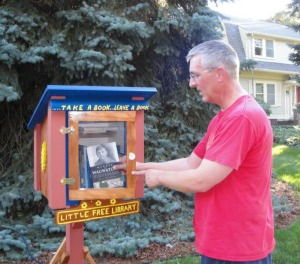 "Here I am placing one of my ""Murder in Wauwatosa"" books in a Free Little Library on Warren Avenue in Wauwatosa this summer. These little libraries are so cool. People come by, pick up a book and leave one."